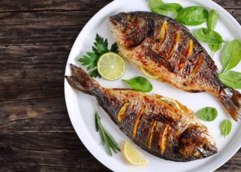 delicious roasted dorado or sea bream fish with lemon and orange slices, spices, fresh parsley and spinach on white platter on old dark wooden table view from above